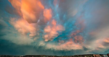 Dramatic sky with thunderclouds. Pink Clouds Illuminated by the Rays of sunset.
