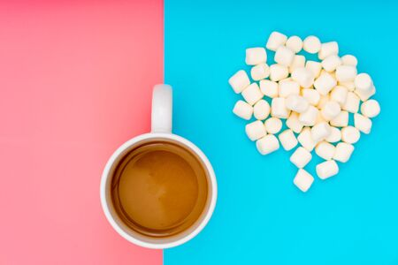 Cup of cocoa on a pink and turquoise background and marshmallows