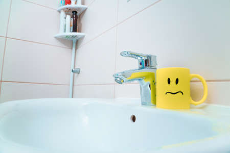 chromed metal faucet for hot and cold water, cup with sad face for toothbrushes in a modern bathroom 写真素材 - 154993764