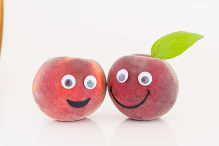 Fruit with a smile and eyes. Smiling peach 写真素材 - 154993767