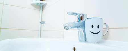 chromed metal faucet for hot and cold water, cup with smile face for toothbrushes in a modern bathroom 写真素材 - 154993768