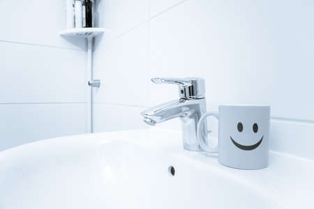 chromed metal faucet for hot and cold water, cup with smile face for toothbrushes in a modern bathroom