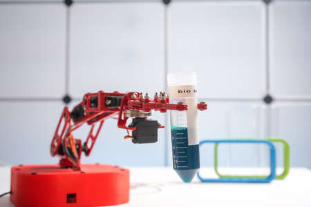 Robot arm with test tube with biological sample in science laboratory