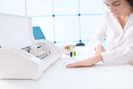 Young woman in printing office insert paper and color pens on plotter