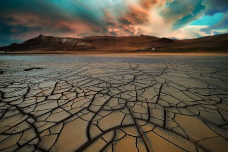 Dried land in the desert. Cracked soil with dramatic sky on the horizon 写真素材 - 154994761