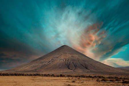 Volcanic mountain on the island of Fuerteventura, Spain. Volcano against the background of a fantastic sky 写真素材 - 154886430