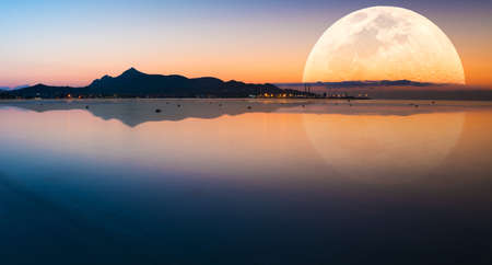 Fantastic landscape with a giant moon against the backdrop of a seascape 写真素材 - 154886386