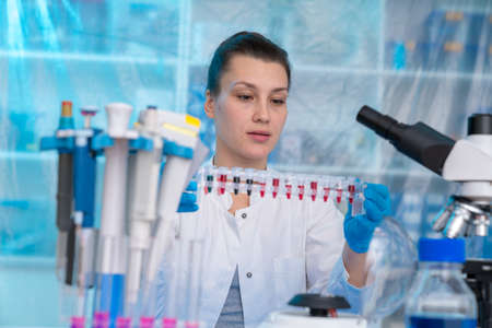 Young woman in clinical lab does PCR test on viral disease