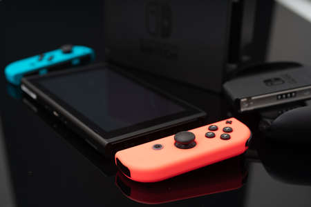 Nintendo Switch video game console developed by Nintendo, released on March 3, 2017 on a black background. Germany, Berlin - June 30, 2019: Nintendo Switch Joy-con controller on a white background 写真素材 - 155013191