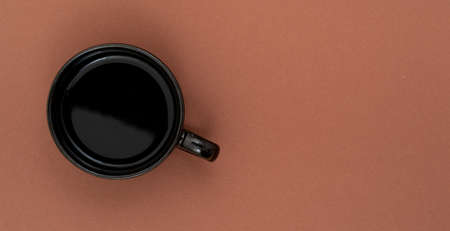 Top view, flat lay of black coffee cup on background brown 写真素材