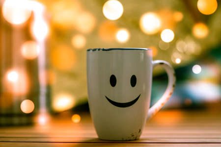 Mug with tea or mulled wine on christmas background with bokeh 写真素材