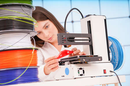 Young female designer working on a prototype device on a 3D printer 写真素材