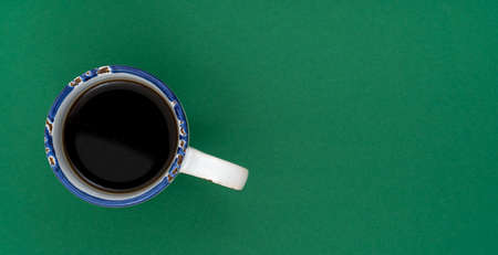 Top view, flat lay of black coffee cup on background green