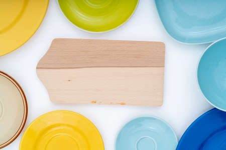 cutting board and ceramic plates on white background flat lay