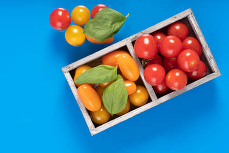 fresh italian cherry tomatoes on the vine in a wooden crate on a background 写真素材