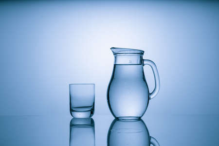 Pitcher with drinking water and a glass with a drink, blue tone 写真素材