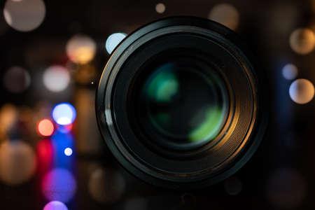 Photo camera lens on dark bokeh background