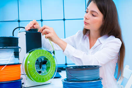 Young woman use 3d printer at office High quality photo