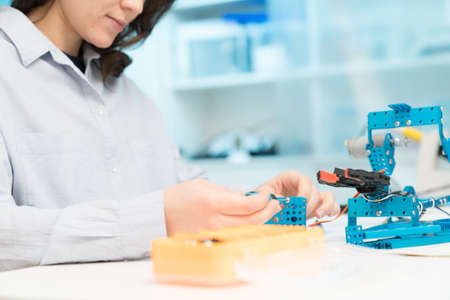 Student woman in robotics laboratory working  on project mechatronics