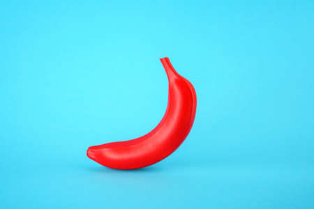 Red banana on a blue background. Fake GMO product concept
