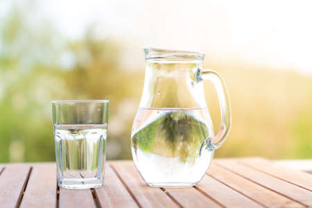 jug with water and a glass on a wooden table on the nature in the garden