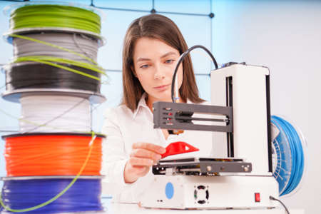 Young female designer working on a prototype device on a 3D printer Фото со стока