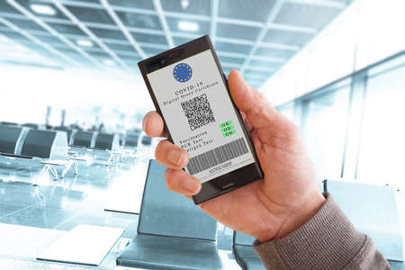 Cell phone with Green Digital Cetrificate. Vaccinated person with digital health passport app in mobile phone for travel during covid-19 pandemic 스톡 콘텐츠