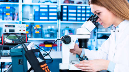 A young woman is testing an electronic module for the production of electric cars. Quality control laboratory with microscope and measuring instruments