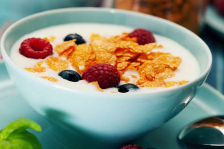 Breakfast of cornflakes and raspberries, blueberries and milk in a blue plate Foto de archivo