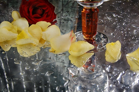 The crystal goblet and a yellow rose petals on a wet table,red rose Stock Photo - 10706928