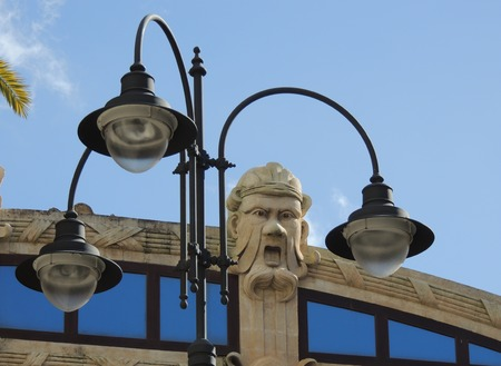 decoration of a building that represents a face that stands out in a light blue sky framed by a lamppost