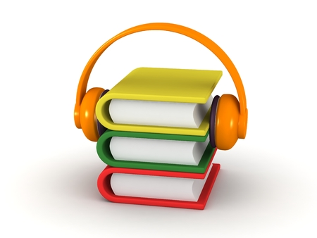 A small stack of books with headphones over them - audiobook concept