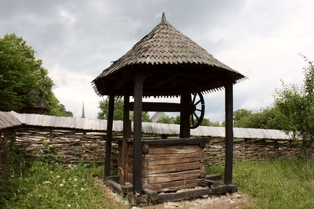 secular: Secular fountain and wall of wood, specific for Transylvania Stock Photo