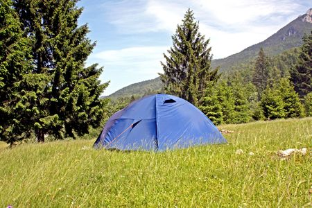 Tent in camping area with mountain landscape in background Stock Photo