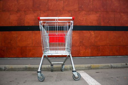 trundle: Empty shopping cart in front of market wall Stock Photo
