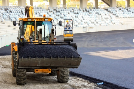 Cluj-Napoca, Romania - August 24, 2011 - Workers smoothing asphalt at Arena stadium from Cluj-Napoca Editorial