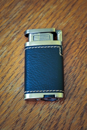 Metallic lighter with leather on the table Stock Photo - 11075091