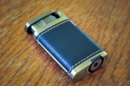 Metallic lighter dressed in leather over a table