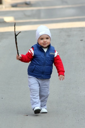 A little kid running with a wood stick in the hand Stock Photo - 12803345