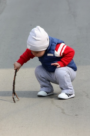 A little kid playing with a wood stick Stock Photo - 12803346