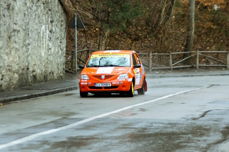 Brasov, Romania - 30.03.2012 - Orange Dacia Logan race rally car on asphalt road competition Stock Photo - 12925797