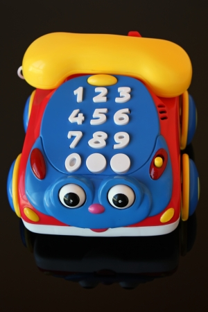 A colorful toy telephone over black background photo