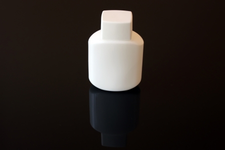 masculin: Bottle of body care product over black background