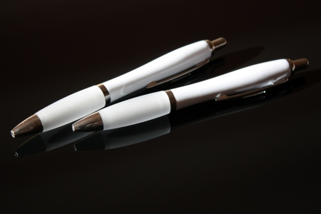 Two ballpoints pens over black background Stock Photo - 16594116
