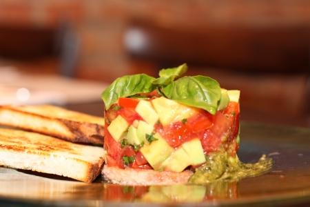 Tomatoes tratar with avocado, garlic and basil