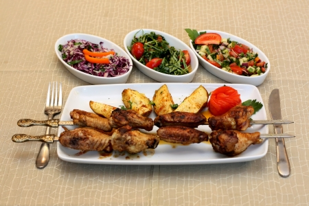 Grilled chicken legs with potatoes and salad photo