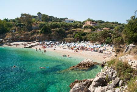 kerkyra: Tourists relaxing on beautiful beach of Kassiopi in the north area of Corfu Island.