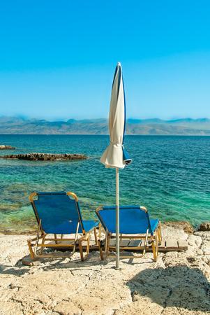 sunbeds: Sunbeds and umbrellas (parasols) on Kassiopi beach in Corfu Island, Greece Stock Photo