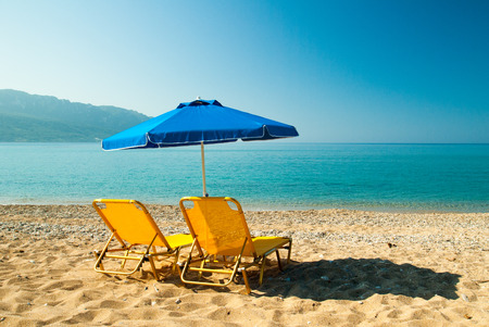 Parasols and sunbeds into the sun on a tropical beach. Stock Photo