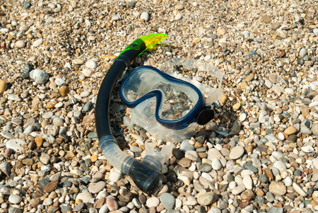 Swim goggles and a snorkel tube lying in the sand near the water on a sunny beach. photo